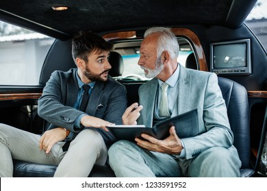 Senior and young businessman in limousine and working together.
