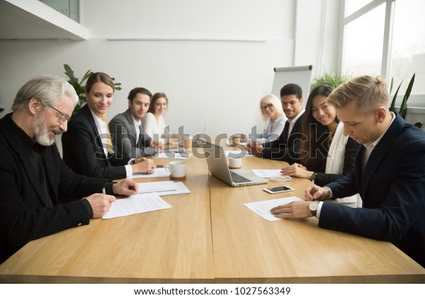 Senior and young businessmen sign contracts at group multiracial meeting, experienced investor buying startup making partnership deal after successful negotiation putting signature on business papers