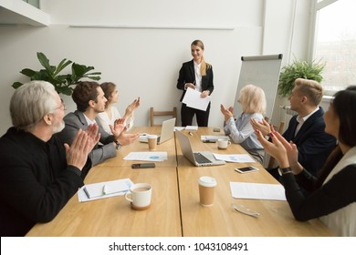 Senior and young businesspeople applauding businesswoman after presentation at conference meeting, grateful group clapping hands cheering smiling team leader, appreciation or congratulation concept