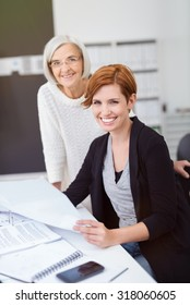 Senior and Young Businesswomen at the Table with Documents Inside the Office, Smiling at the Camera.