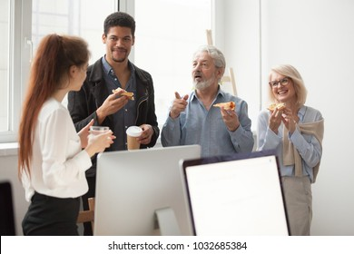 Senior and young diverse colleagues talking eating pizza together in office, older aged executives sharing meal with employees, smiling staff team people enjoying lunch time or coffee break