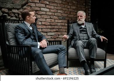 Senior and young gentlemen having conversation
