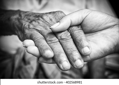 Senior and young holding hands with black and white effect