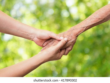 Senior and young holding hands on abstract nature background.