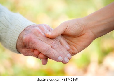 Senior and young holding hands outside