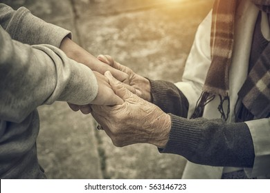 Senior and young holding hands with retro effect