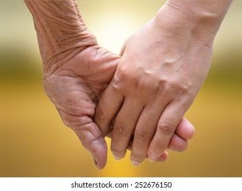 Senior and young holding hands at sunset.