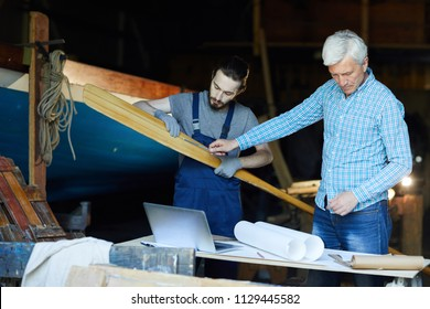 Senior and young shipbuilding engineers working over wooden paddle for boat or other vessel in workshop