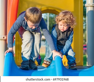 Senior and younger brothers ride the slides on the playground