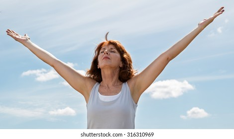 senior zen - thinking beautiful mature woman opening her chakra and arms wide,seeking for harmony and wellbeing outdoors in summer daylight