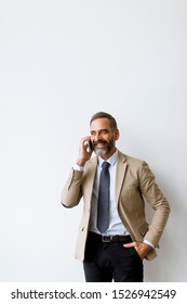 Seniorbearded businessman using mobile phone against wall in office