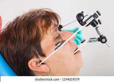 Seniorpatient wearing a  facebow for transfer functional and aesthetic components from patient's mouth to the dental articulator