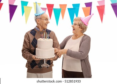 Seniors With Cake And Party Hats Celebrating A Birthday Looking At Each Other Isolated On