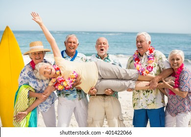 Seniors carrying senior woman on a sunny day