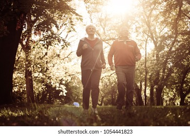 Seniors couple exercising together in meadow.