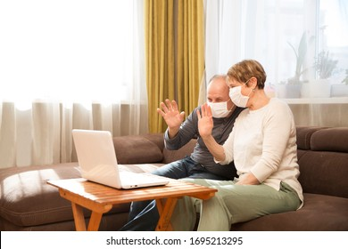 Seniors couple  grandmother and grandfather wearing medical face mask and using laptop Communicate with grandchildren online at home. quarantine. standing in home. chelter in place.