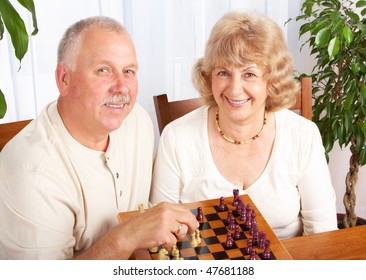 Seniors couple  playing chess at home
