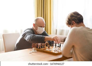 Seniors couple  wearing medical face mask play chess in home. quarantine. health concept. Corona Virus.