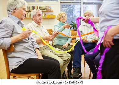 Seniors with dementia do an exercise with colorful ribbons for interaction