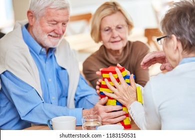 Seniors with dementia play with building blocks and build a tower in the nursing home