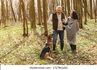 Seniors in a forest. People walks. Family with dog.