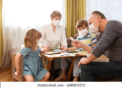 Seniors grandparents with grandsons wearing medical face mask playing  board game together at home. quarantine. health concept. Corona Virus. Family having fun playing at home. stay home concept