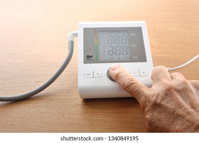Senior's hand finding the indicators result on the screen of digital blood pressure monitor.
