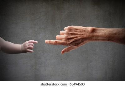 Senior's hand touching a little child's hand