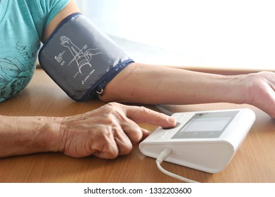 Senior's hand try to measure her blood pressure and digital heart rate.Elderly care concept.