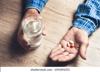 Senior's hands, a glass of water and pills are lying on the table. Painful old age. Health Care for the Elderly