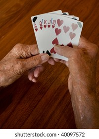 seniors hands holding a winning plaing card hand of a straight flush of hearts