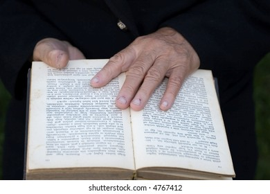 Senior's hands on old book