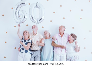 Seniors holding big silver balloons at their friend's birthday party
