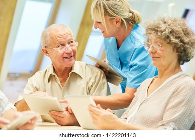 Seniors learn with the Tablet PC supported by caregiver in the computer course