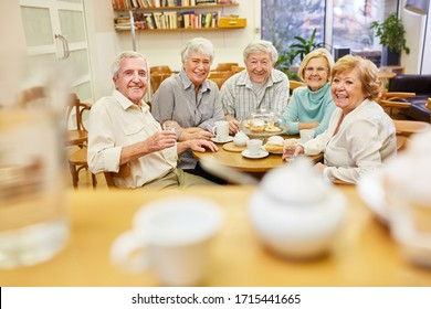 Seniors as pensioners and friends drink coffee together in the retirement home