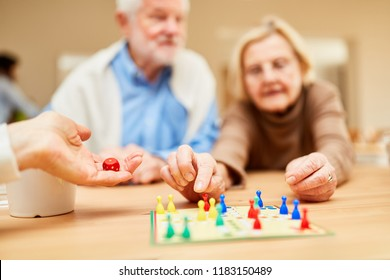 Seniors play a board game as a dice game as employment in the retirement home