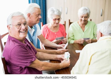 Seniors playing cards together in a retirement home