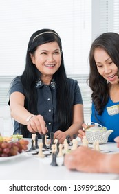 Seniors playing chess and drinking tea at home