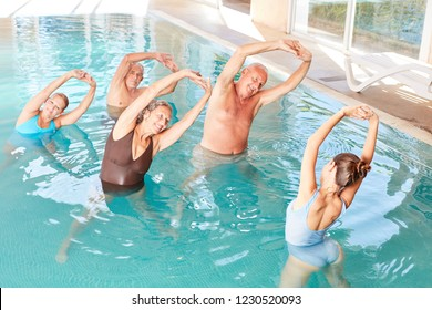 Seniors in the pool doing water aerobics in a workshop in rehab