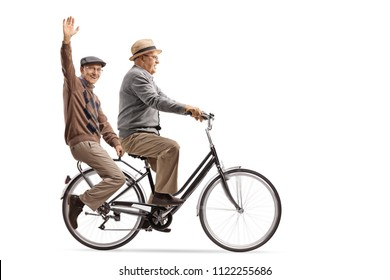 Seniors riding on a bicycle with one of them waving at the camera isolated on white background