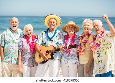 Seniors singing and playing guitar on a sunny day