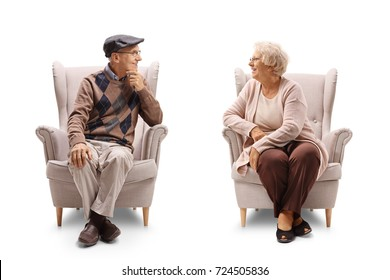 Seniors sitting in armchairs and having a conversation isolated on white background