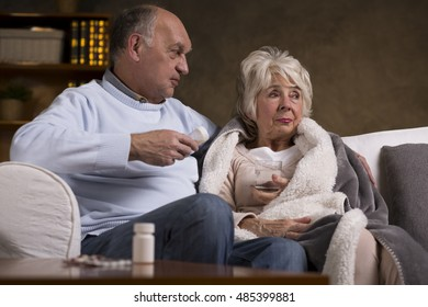 Seniors sitting on the couch and taking medicaments