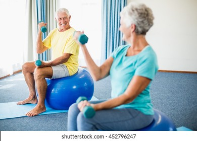 Seniors using exercise ball and weights in a studio