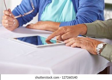 Seniors using the internet with tablet computer and a finger on the touchscreen