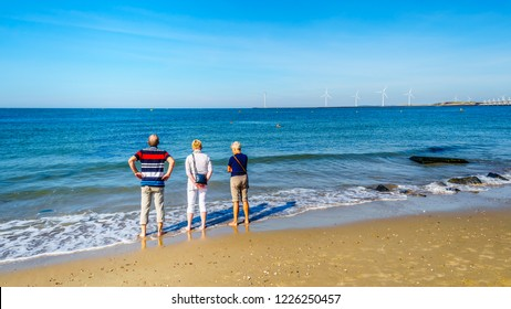 Seniors wading in the Noodzee at the sandy beach of Banjaardstrand along the Oosterschelde inlet at the Schouwen-Duiveland peninsula in the province of Zeeand in the Netherlands