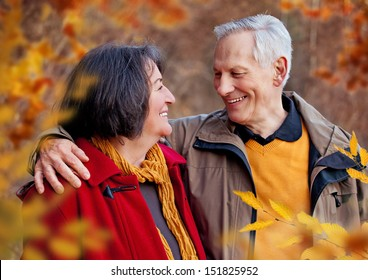 seniors walking in autumn forest / hugging