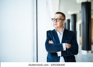 Seniow businessman with crossed hands standing and thinking by the windows in office.