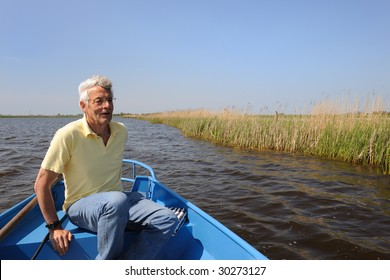 Senoir man is with boat in polder nature