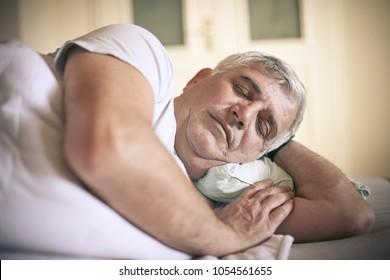 Senor man sleeping on bed at home. Close up.
